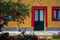 View of a typical colorful house of Linosa, colored red and orange with green door