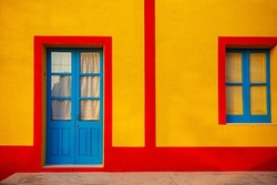 View of a typical colorful house of Linosa, colored red and yellow with blue door and window