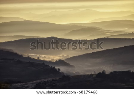 Stock Photo view of a valley in a beautiful early morning with fog between hills