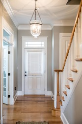 View of a white front door entrance in a new construction house with a hanging chandelier clear glass light and a staircasefrom the interior