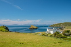 View of a white house among green fields and hills with small rocky island on the ocean behind it, Isle of Skye, Scotland, United Kingdom