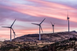 View of a wind turbines on top of mountains, dramatic sunset sky, in Portugal.
