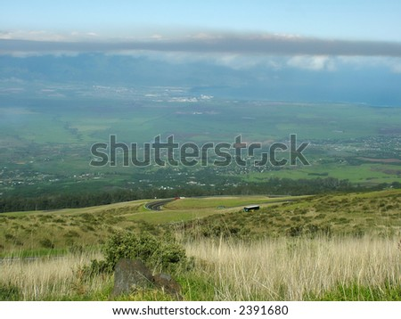 View of a winding mountain road that leads above the clouds