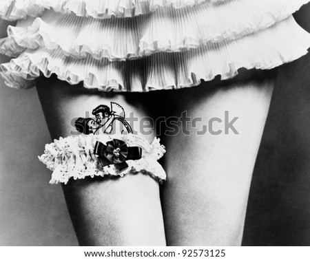 View of a woman hiding a tattoo with a garter on her thighs - stock photo