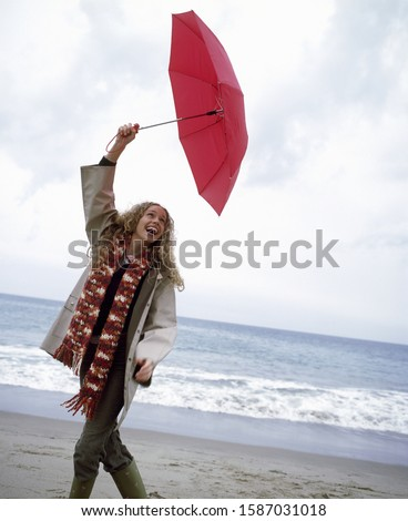 View of a woman holding up a red umbrella on the beach