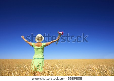 view of a woman in green dress with flower and wide valley ahead - stock photo