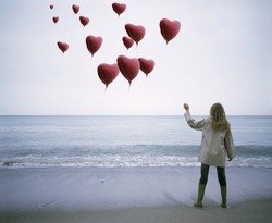 View of a woman letting heart-shaped balloons go on the beach