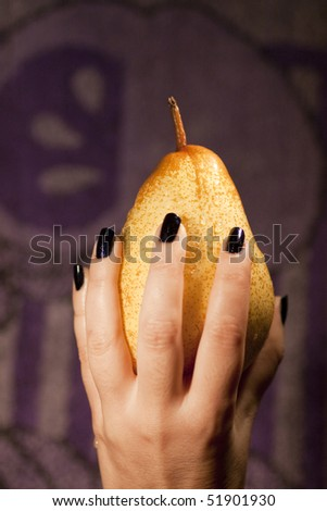 View of a woman's hand holding a wet pear.