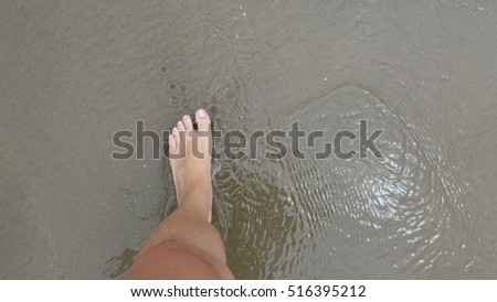 View of a woman's leg when looking down while walking on beach #516395212
