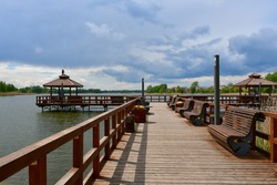 View of a wooden marina, pier or platform with handles and floor made out of boards or logd with a small shack or hut for relaxation located next to river or lake seen before the storm in Poland