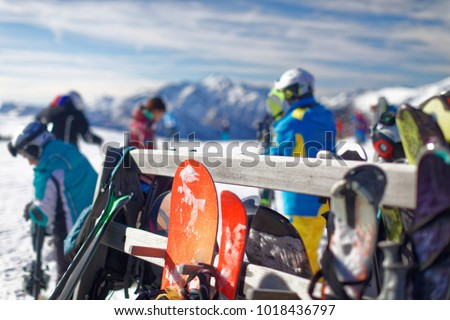 View of a wooden rack for skis, full of skis and snowboards, on the top of a high mountain with the beautiful landscape of dolomiti mountains and people skiing, alpe tognola, san martino di castrozza #1018436797