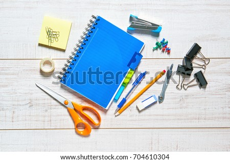 View of a wooden table with a notebook, pen, pencil, rubber, scissors, sellotape, calipers, stapler, clips and pins.