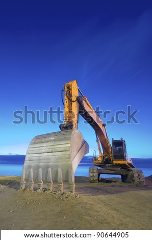 view of a yellow backhoe  on a beach at sunrise