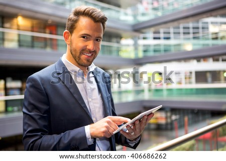 View of a Young attractive business man using tablet #406686262