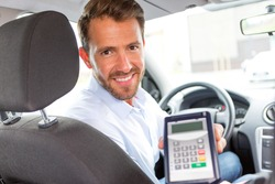 View of a Young attractive driver ask customer for payment in car