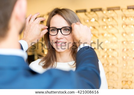 View of a Young attractive  woman testing new glasses with optician #421008616