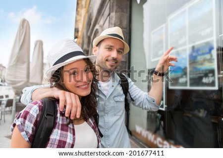 View of a Young happy couple in front of travel agency
