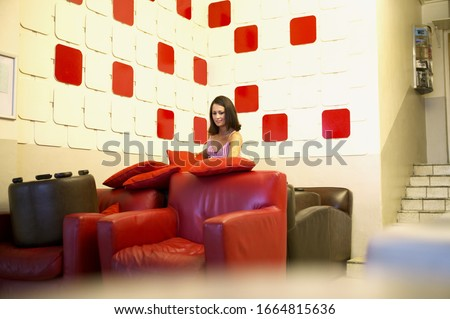 View of a young woman in a room with armchairs and red squares on the walls