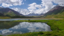 View of Achik Tash base camp of Lenin Peak nowadays Ibn Sina in the snow-capped Trans-Alai mountain range in southern Kyrgyzstan with lake in foreground