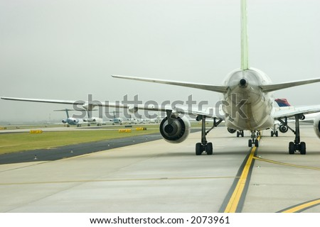 View of airplanes lined up for takeoff under another airplane's wing
