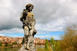 View of Albi (France). Statue of Bacchus (Dionysus) with grapes and wine cup at Bishop palace park in Albi (Roussillon-Languedoc) and view of  city and Tarn river with its bridges.