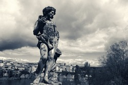 View of Albi (France). Statue of Bacchus (Dionysus) with grapes and wine cup at Bishop palace park in Albi (Roussillon-Languedoc) and view of  city and Tarn river with its bridges. Toned photo.