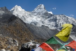 View of Ama Dablam from Ama Dablam Basecamp (4.570m) in Nepal with prayer flags in the foreground