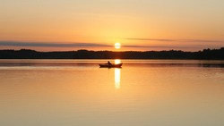 View of amazing sundown over water and rowboat in sun path