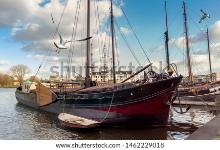 View of Amsterdam - old wooden sail ships moored in the harbor of Oosterdok near the Maritime Museum. Dutch quay with vintage sailing vessels. Stockfoto ©