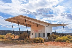 View of an abandoned gas station in the middle of the desert on the West Coat of the United States of America; building in retro style with large canopy
