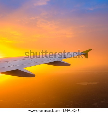 View of an airplane wing against a beautiful sunrise sky