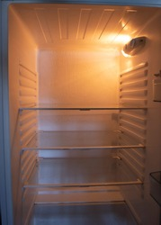 View of an empty fridge with yellow light