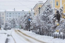 View of an empty snow-covered city street during a snowfall. Snowy road. Fresh white snow on tree branches. Cold snowy winter weather. City of Magadan, Magadan Region, Siberia, Far East of Russia.