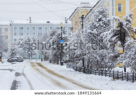 Photo of  View of an empty snow-covered city street during a snowfall. Snowy road. Fresh white snow on tree branches. Cold snowy winter weather. City of Magadan, Magadan Region, Siberia, Far East of Russia.