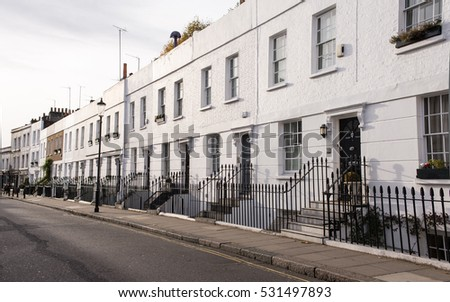 View of an empty street in the residential area of Chelsea, London, UK with Victorian white residential buildings with black doors and metal fence.