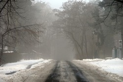 View of an icy slippery road during thaw. Ice on road. Ice on pedestrian walk. Glazed frost during thaw. Poland, Europe
