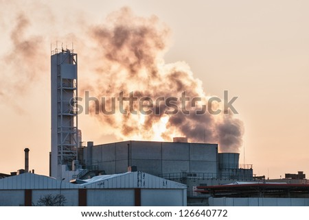view of an oil refinery with smoking chimneys in winter against the sun