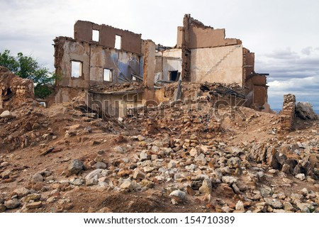 View of an old ruined house over a pile of rubble. House in ruins.