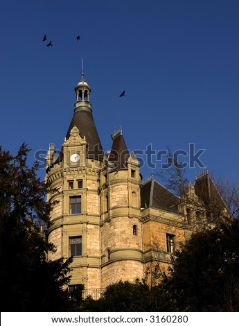 View of an old swiss mansion with crows flying over it.Sunset light. - stock photo