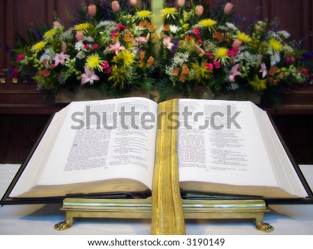 View of an open Bible on an altar, flowers in the background