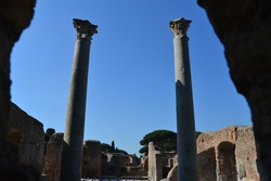 view of ancient roman temple with blue sky and two ancient colums in the archeological site of ostia antica rome italy
