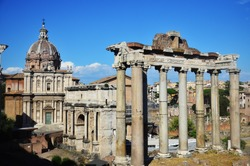 View of ancient structures in the imperial forum of Rome. The standing columns belong to the temple of Saturn. Behind it is the triumphal arch of Septimius Severus. Roman empire. Travel in Italy.