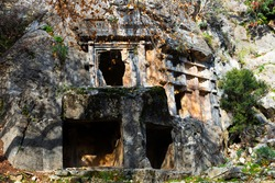 View of antique rock burial chambers in ancient Lycian city of Pinara in Turkey. Examples of ancient rock cut architecture ..