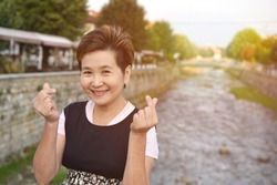 View of asian woman showing mini-love sign near Sinan Pasha Mosque that was declared a Monument of Culture of Exceptional Importance in 1990 by the Republic of Serbia. Prizren Kosovo.