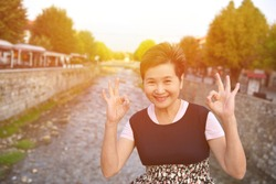 View of asian woman showing okay sign near Sinan Pasha Mosque that was declared a Monument of Culture of Exceptional Importance in 1990 by the Republic of Serbia. Prizren Kosovo.
