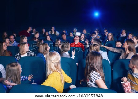 View of audience watching film in movie theatre. Boy in virtual glasses sitting in centre. Curious  spectators looking at him. Projector light source. Concept of gadgets, cinematography.