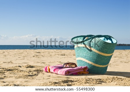 View of bag, towel and sunglasses on the beach.