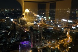 View of Bangkok city seen from inside a hotel room at night