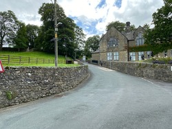 View of Bank Lane, as it runs through Giggleswick, with dry stone walls, and old buildings in, Settle, Yorkshire, UK
