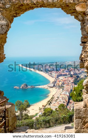 stock photo view of beach and village blanes through a stone arch of the st john castle costa brava span 419263081 - Каталог — Фотообои «Балконы, арки»